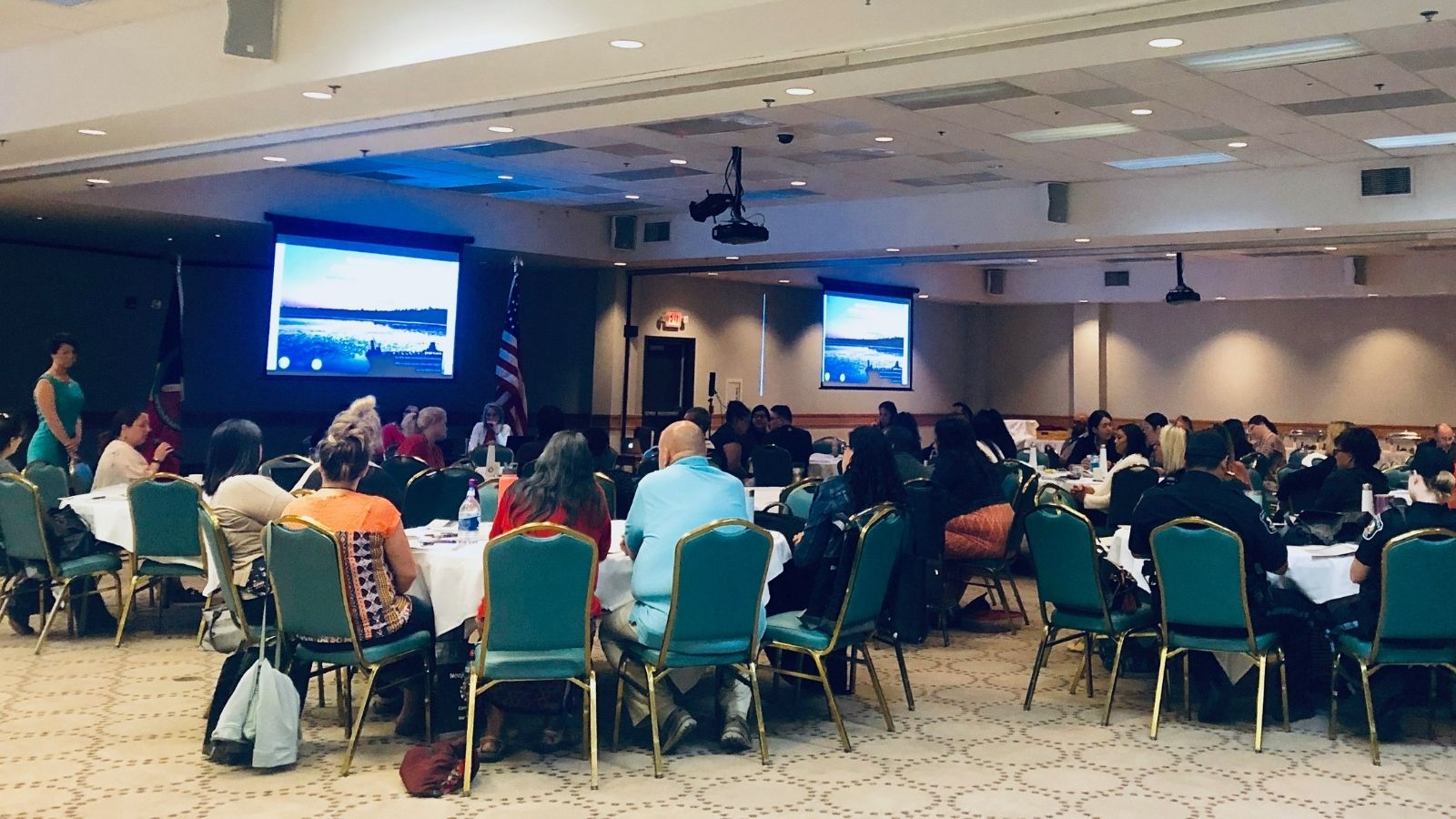 Group of advocates and tribal leaders seated at tables participating in Bay Mills Indian Community training watching presentation on screen.