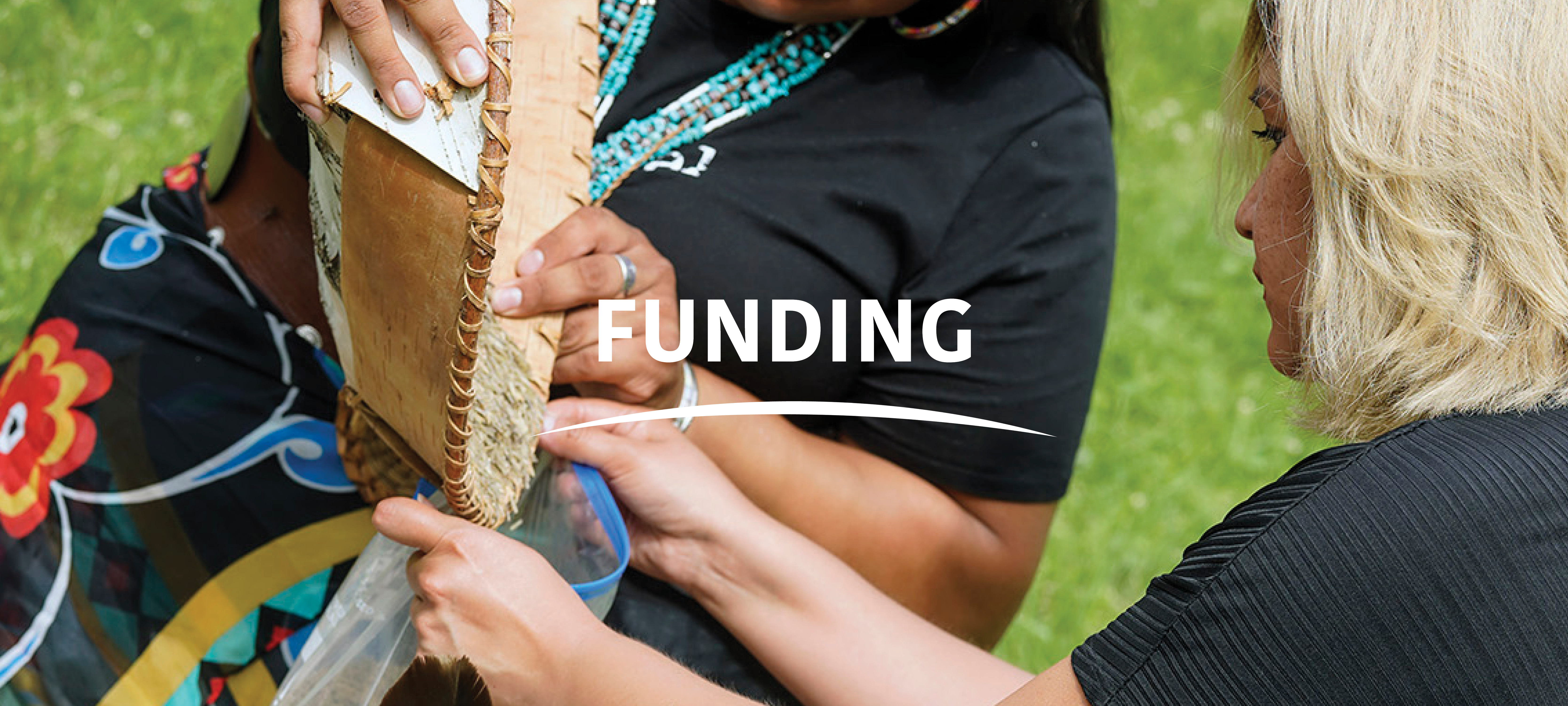 """Two Indigenous women standing with first woman on left pouring basket of wild rice into plastic bag held by second woman on right, with text in center """"Funding"""" with white curved line beneath text."""