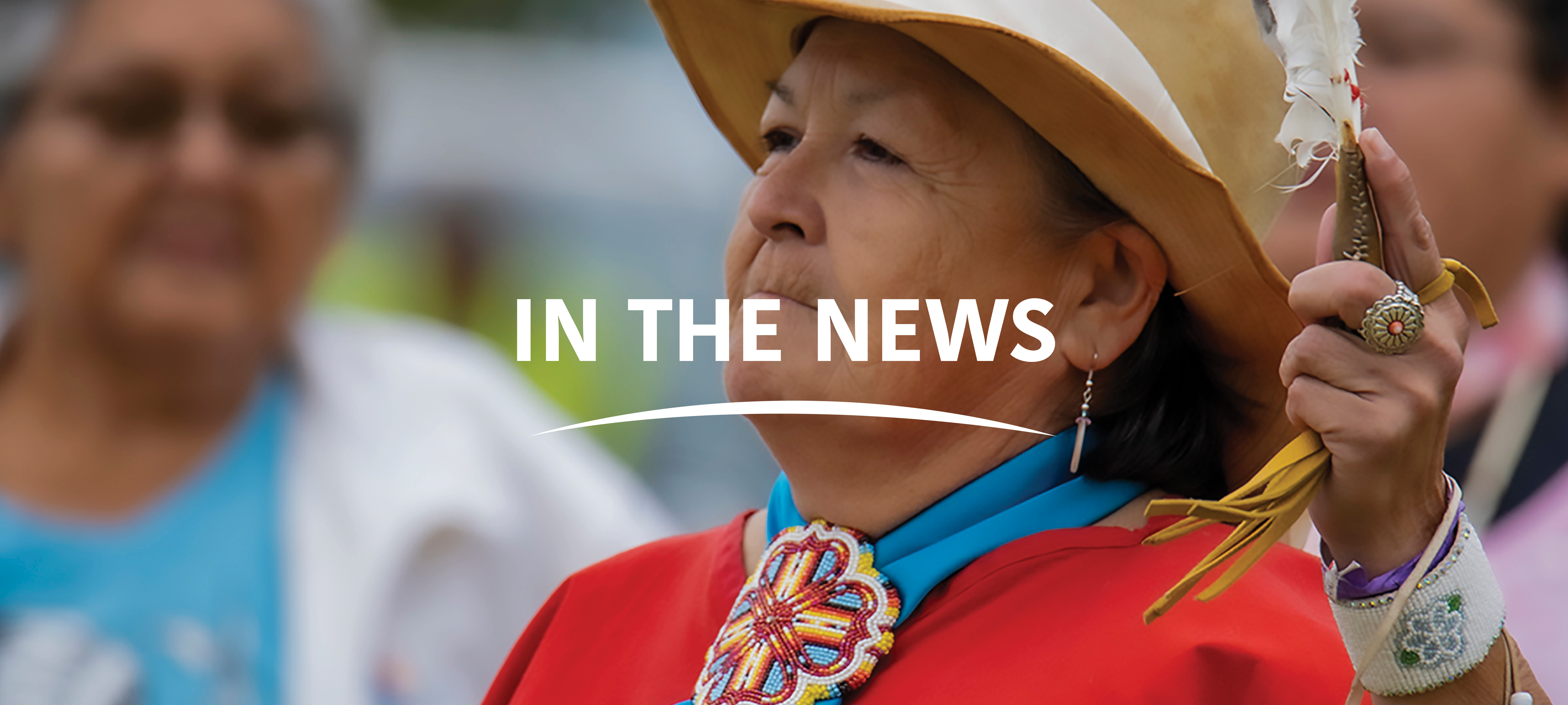 """Indigenous woman in a tan hat and red blouse and teal scarf with beaded medallion holding feather up in left hand looking forward, with text in center """"In the News"""" with white curved line beneath text."""